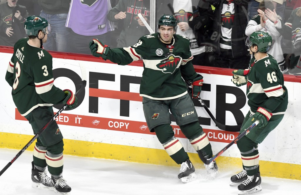 Minnesota Wild's Charlie Coyle (3) and Jared Spurgeon (46) move in to celebrate the goal of Luke Kunin, center, against the Detroit Red Wings in the f