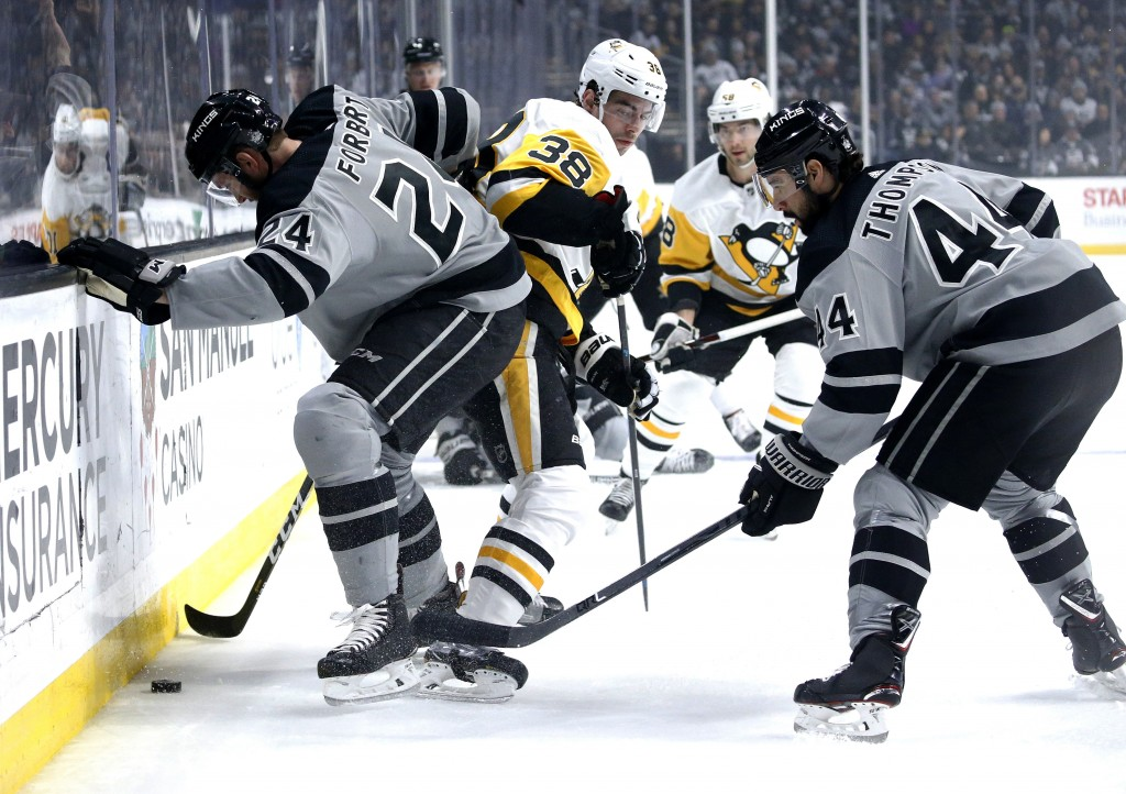 Pittsburgh Penguins forward Derek Grant, center, vies with Los Angeles Kings defenseman Derek Forbort, left, and forward Nate Thompson during the firs