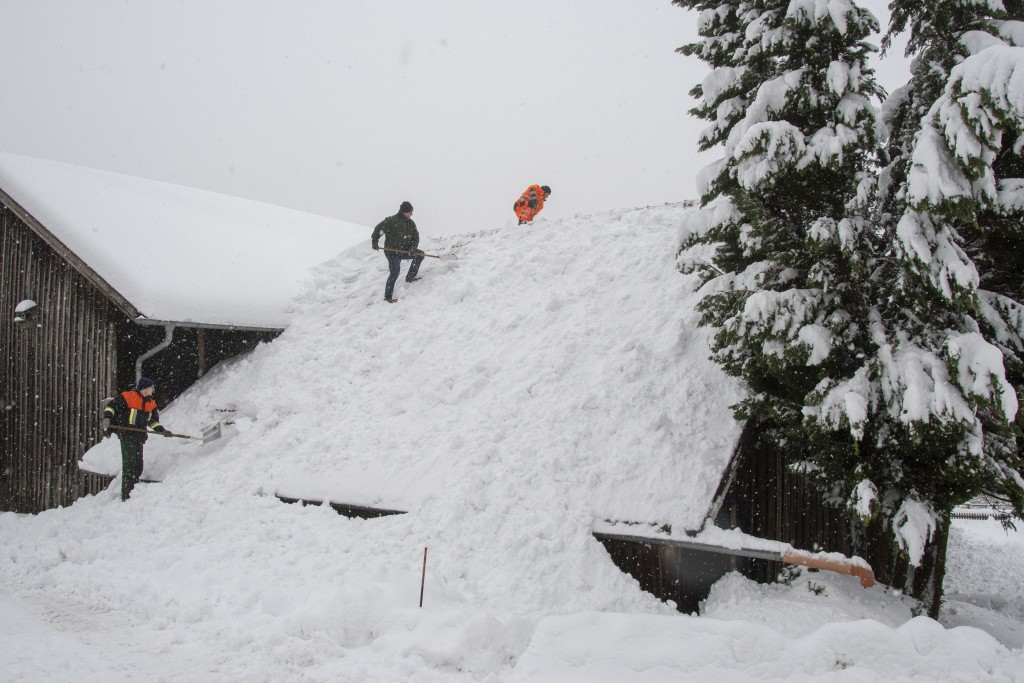 Men remove snow from the roof of a building in Elisabethszell, Germany, Sunday, Jan. 13, 2019. (Armin Weigel/dpa via AP)