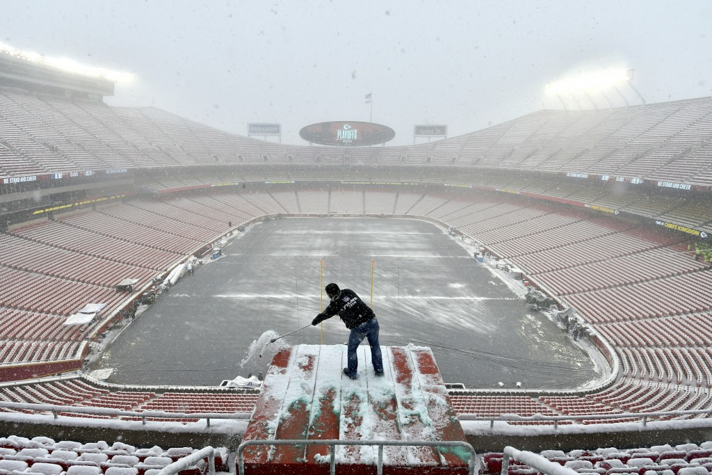 Kyle Haraugh, of NFL Films, clears snow from a camera location at Arrowhead Stadium before an NFL divisional football playoff game between the Kansas
