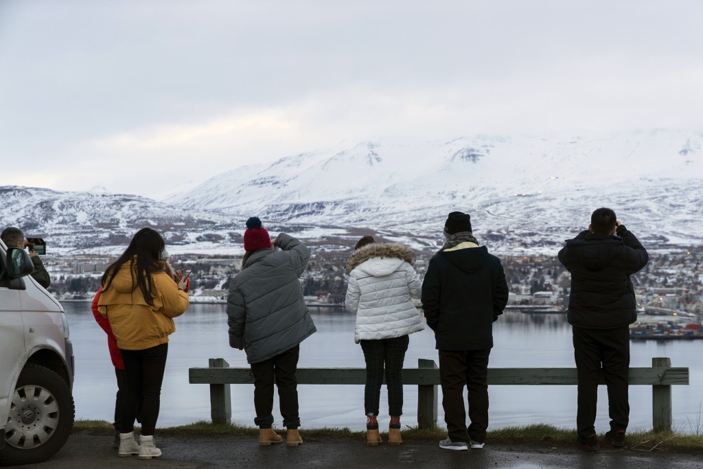 Tourists park their rental car to capture a landscape vista of the Akureyri town, a regional capital in northern Iceland, on Dec. 19, 2018.  Police in
