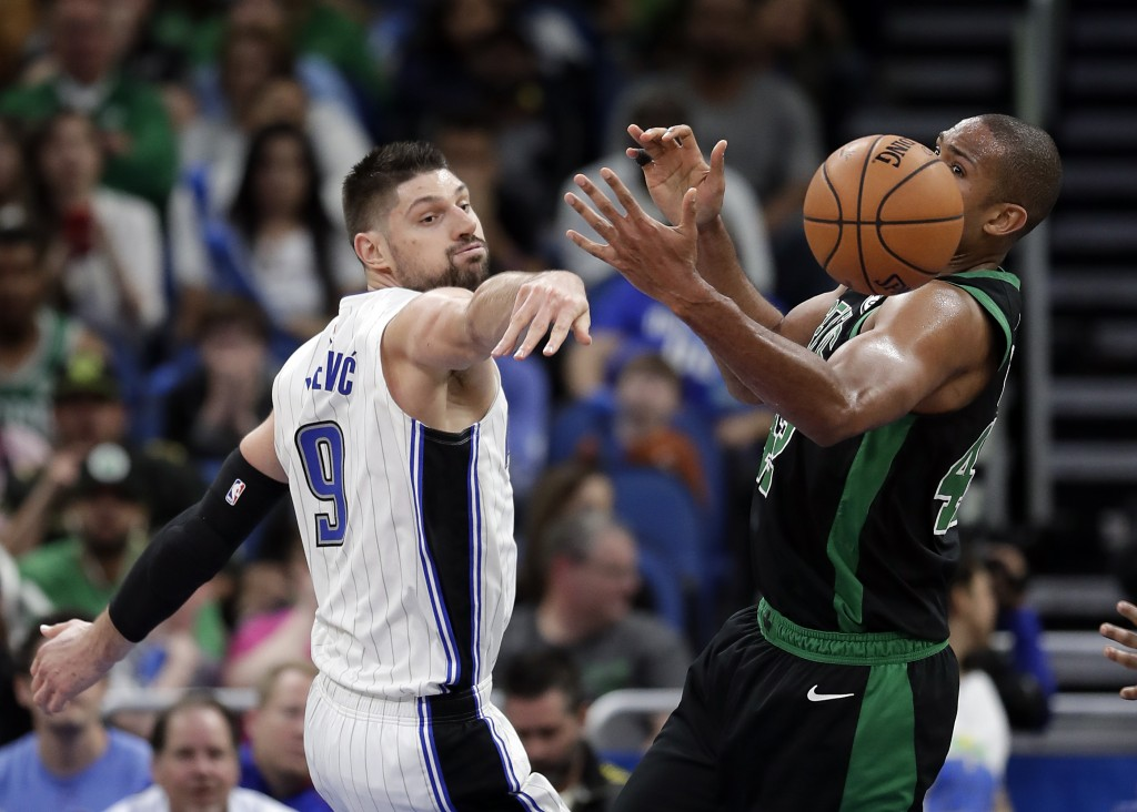 Orlando Magic's Nikola Vucevic (9) goes after a loose ball of a rebound against Boston Celtics' Al Horford, right, during the second half of an NBA ba