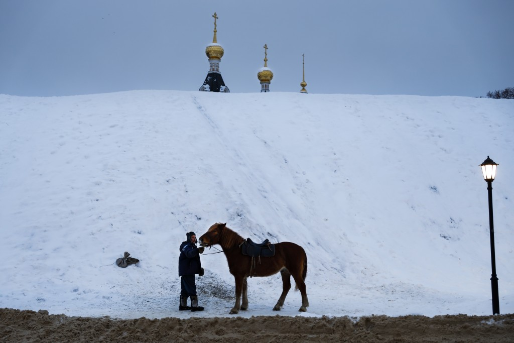 A man prepares a horse to ride tourists during a cold winter day at a hill, near the Assumption Cathedral built in XVI century in the background, in t