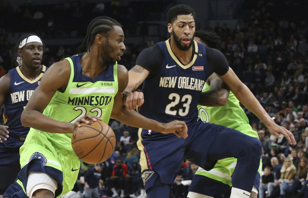 Minnesota Timberwolves' Andrew Wiggins, left, drives past New Orleans Pelicans' Anthony Davis in the first half of an NBA basketball game Saturday, Ja