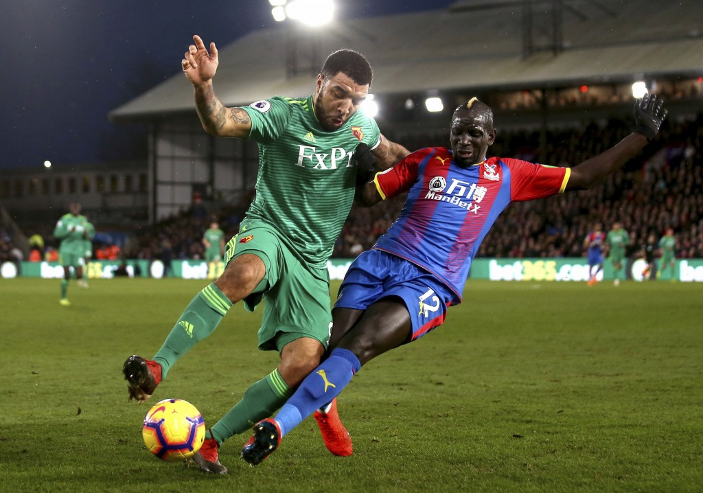 Watford's Troy Deeney, left, and Crystal Palace's Mamadou Sakho fight for the ball during the English Premier League soccer match between Crystal Pala...