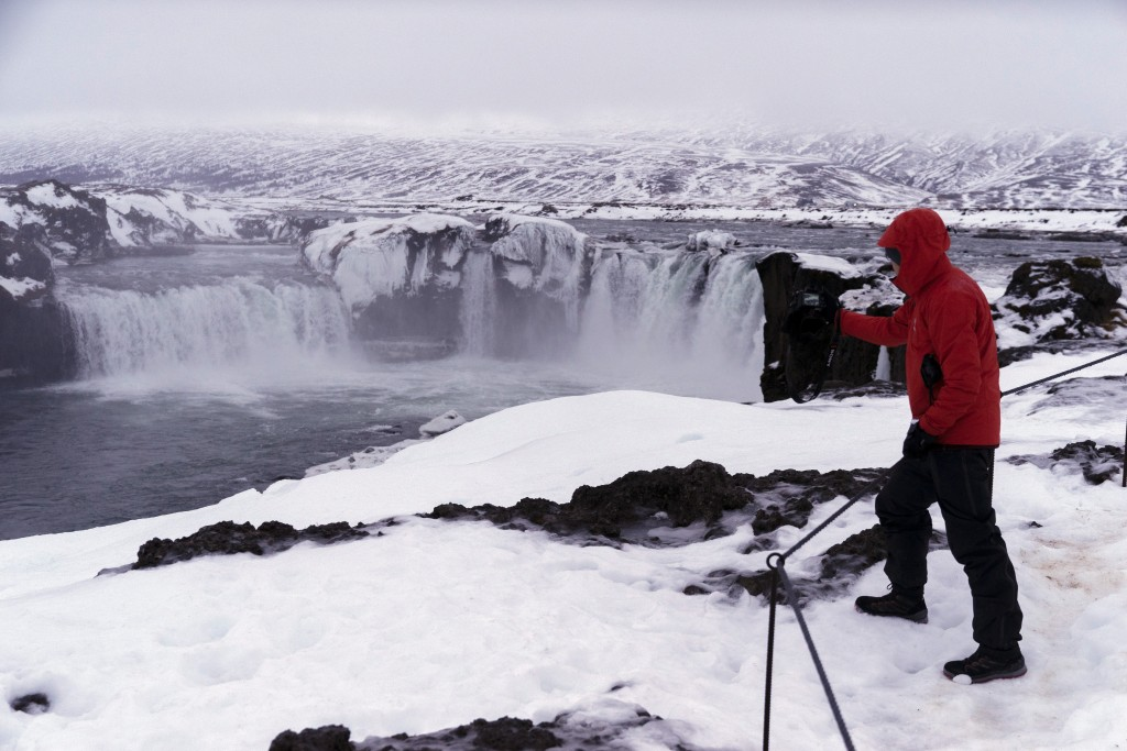 A tourist from Singapore photographs the Godafoss waterfall, a landmark view in northern Iceland, Dec. 16, 2018. Police in Iceland say tourists are of