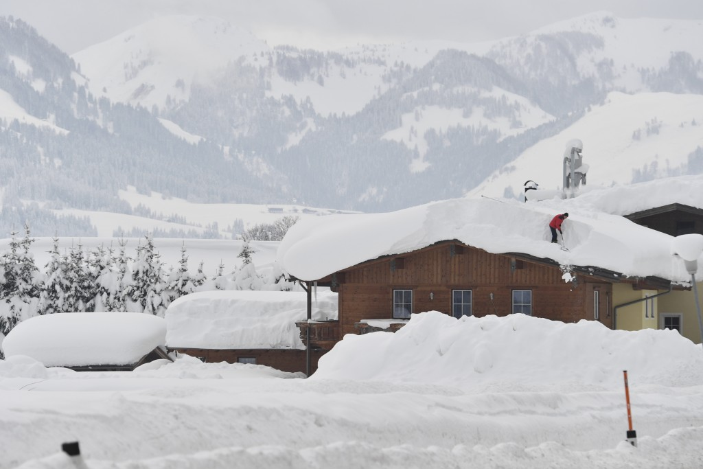 A man cleans snow from a roof on Saturday, Jan. 12, 2019 in St. Jakob, Austrian province of Tyrol.(AP Photo/Kerstin Joensson)