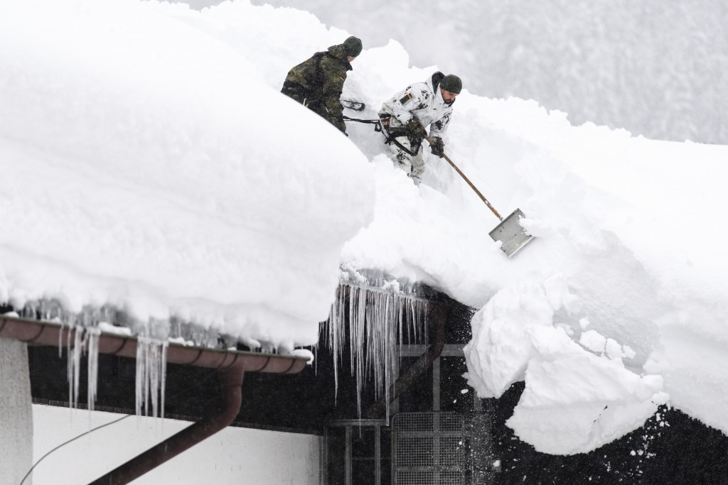 Soldiers of the German forces, Bundeswehr, remove snow from the roof of a building in Buchenhoehe, Germany, Sunday, Jan. 13, 2019. (Matthias Balk/dpa