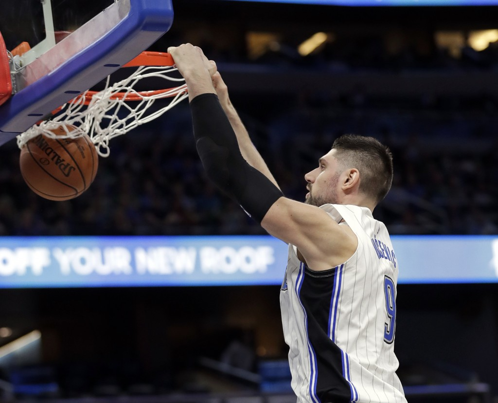 Orlando Magic's Nikola Vucevic makes an uncontested dunk against the Boston Celtics during the first half of an NBA basketball game, Saturday, Jan. 12