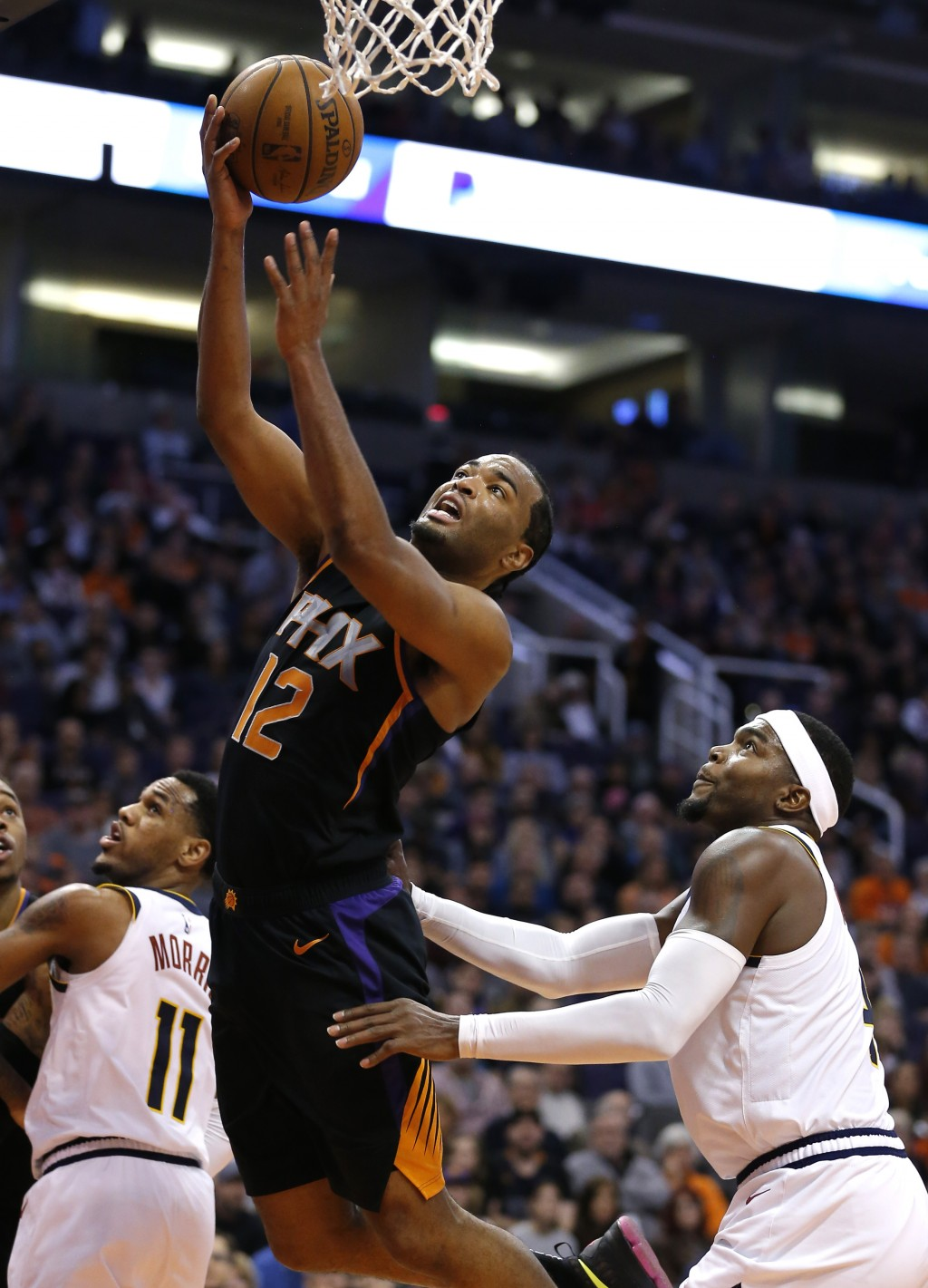 Phoenix Suns forward T.J. Warren (12) drives past Denver Nuggets forward Paul Millsap in the second half during an NBA basketball game, Saturday, Jan.