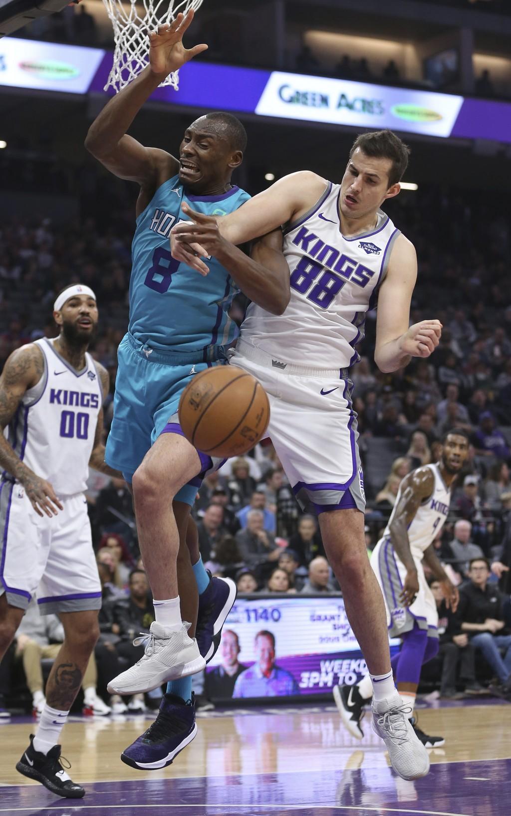 Charlotte Hornets center Bismack Biyombo, left, and Sacramento Kings forward Nemanja Bjelica, right, battle for the rebound during the first quarter o