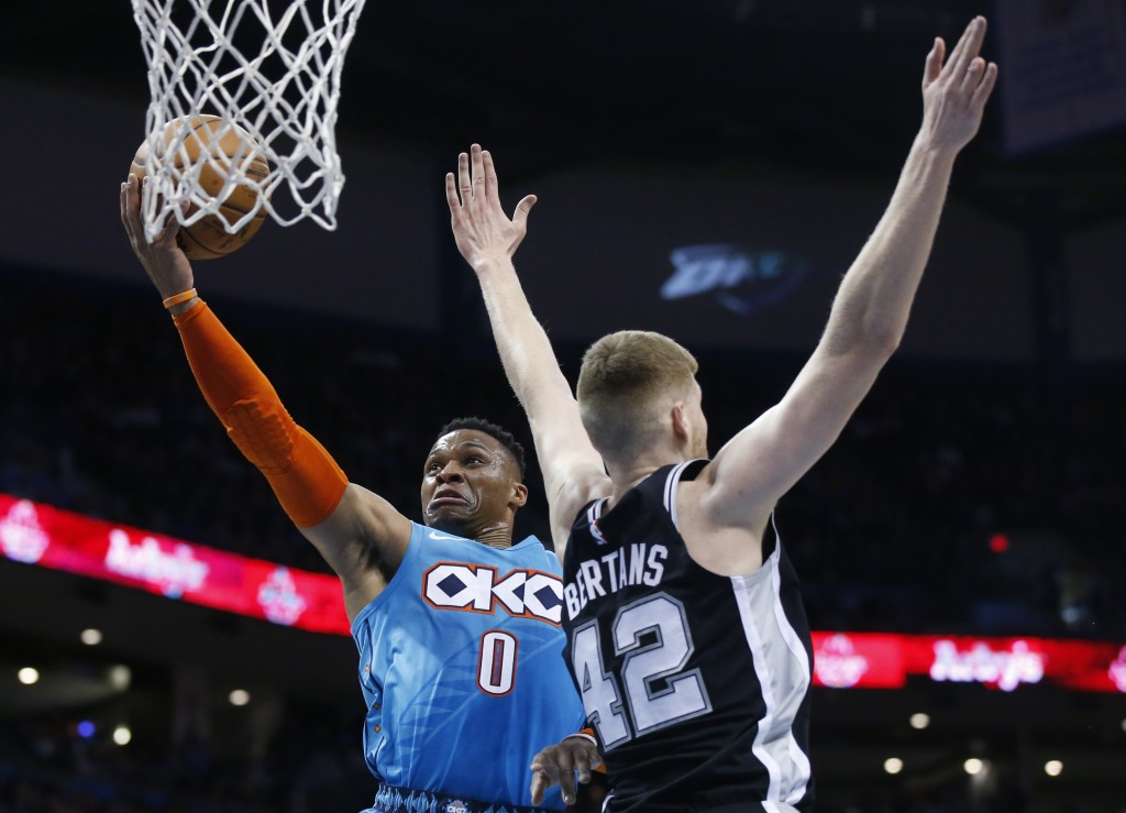 Oklahoma City Thunder guard Russell Westbrook (0) drives to the basket past San Antonio Spurs forward Davis Bertans (42) in the first half of an NBA b