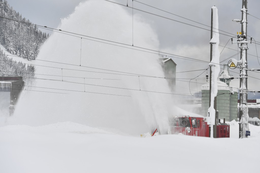 A railway cleans snow from the rails on Saturday, Jan. 12, 2019 in Hochfilzen, Austrian province of Tyrol.(AP Photo/Kerstin Joensson)