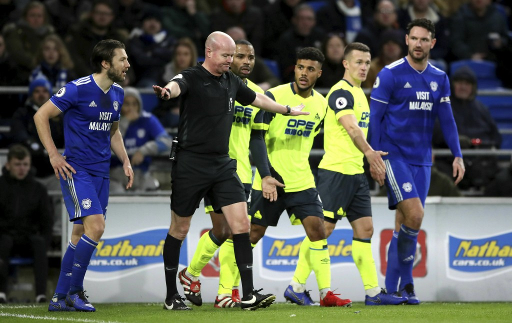 Match referee Lee Mason, center, overturns a penalty decision during the English Premier League soccer match between Cardiff City and Huddersfield Tow