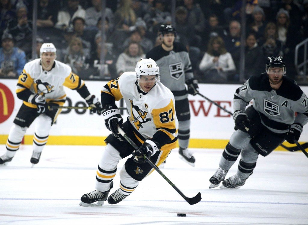 Pittsburgh Penguins forward Sidney Crosby, front, controls the puck during the first period of the NHL hockey team's game against the Los Angeles King