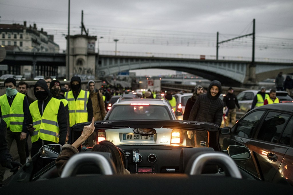 Demonstrators wearing yellow vests walk on the highway in Lyon, central France, Saturday, Jan. 12, 2019. Authorities deployed thousands of security fo