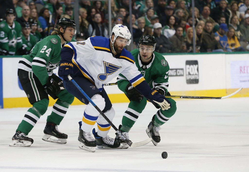 St. Louis Blues left wing Pat Maroon (7) tries to get the puck past Dallas Stars left wing Roope Hintz (24) and center Devin Shore (17) during the fir