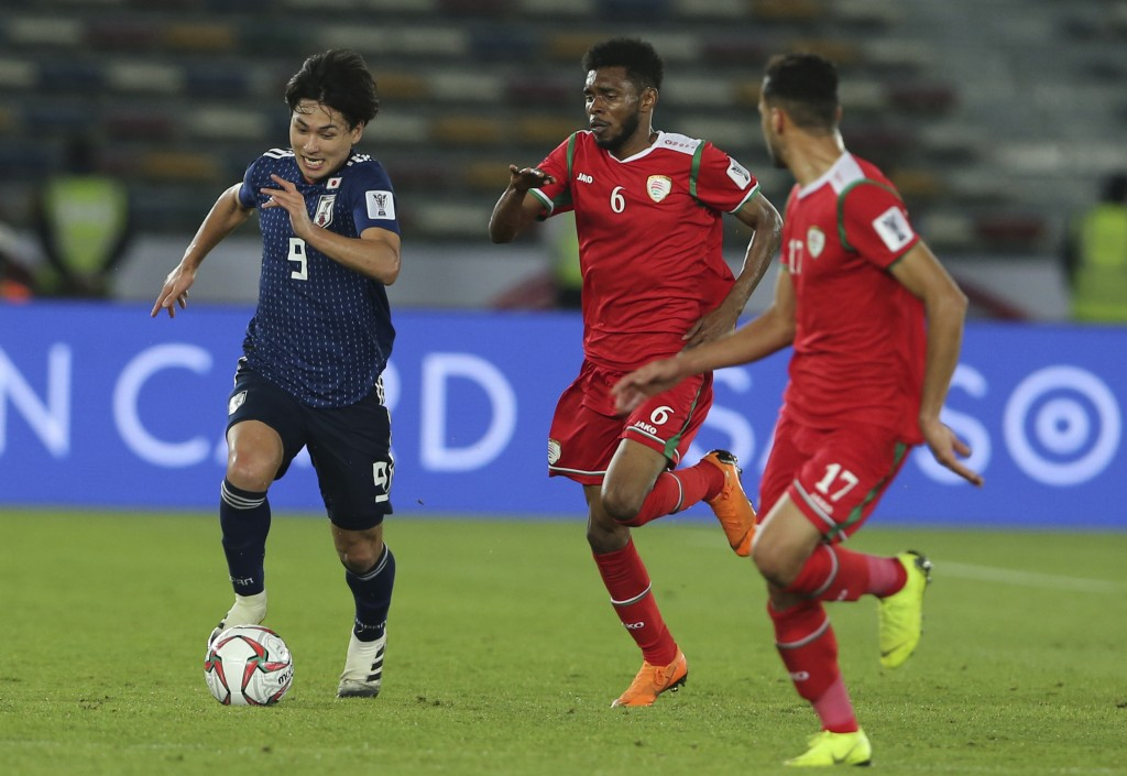 Japan's forward Takumi Minamind, left, challenges for the ball against Oman's midfielder Raed Saleh, center, during the AFC Asian Cup group F soccer m
