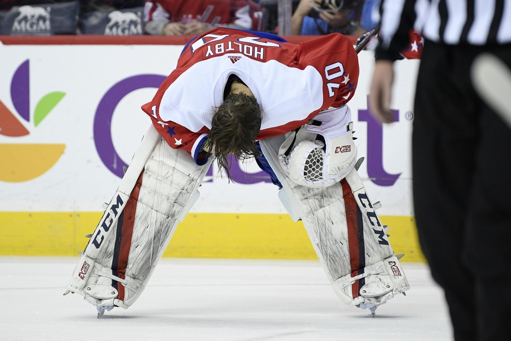 Washington Capitals goaltender Braden Holtby (70) pauses on the ice after he was injured during the second period of an NHL hockey game against the Co
