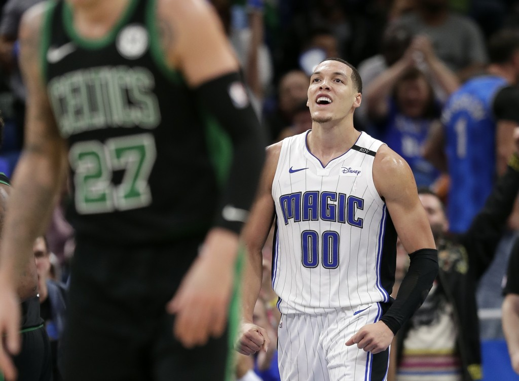 Orlando Magic's Aaron Gordon (00) celebrates after dunking the ball as Boston Celtics' Daniel Theis (27) runs back on offense during the second half o