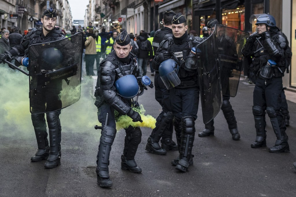 A French riot policeman throws a canister of smoke during clashes with yellow vest protesters in Lyon, central France, Saturday, Jan. 12, 2019. Author