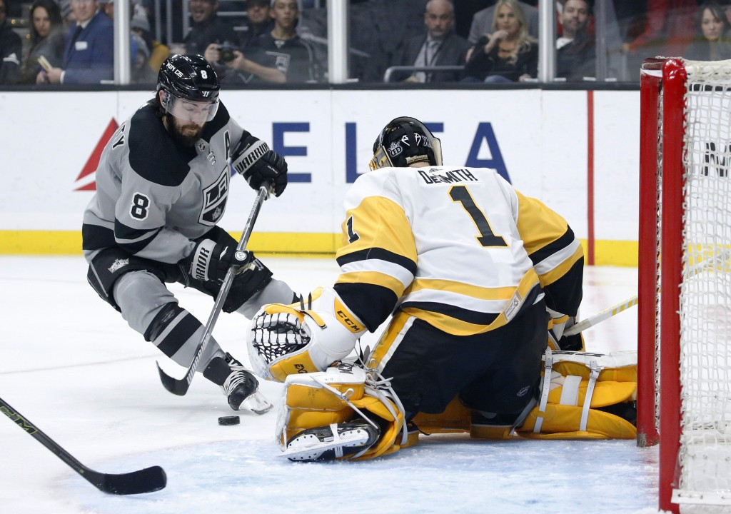 Los Angeles Kings defenseman Drew Doughty, left, shoots as Pittsburgh Penguins goalie Casey DeSmith defends during the second period of an NHL hockey