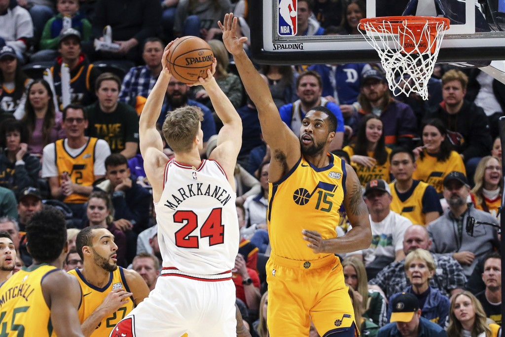 Chicago Bulls forward Lauri Markkanen (24) shoots over Utah Jazz forward Derrick Favors (15) during the first quarter of an NBA basketball game Saturd