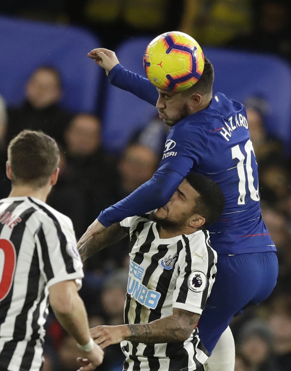 Chelsea's Eden Hazard jumps for a header over Newcastle United's DeAndre Yedlin during the English Premier League soccer match between Chelsea and New