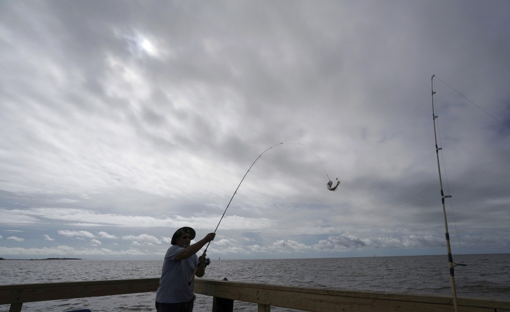 FILE - In this Sept. 5, 2018 file photo, Tim Hitchens, of Gulfprort, Miss., pulls in a fish while fishing from a pier in the Gulf of Mexico, the morni
