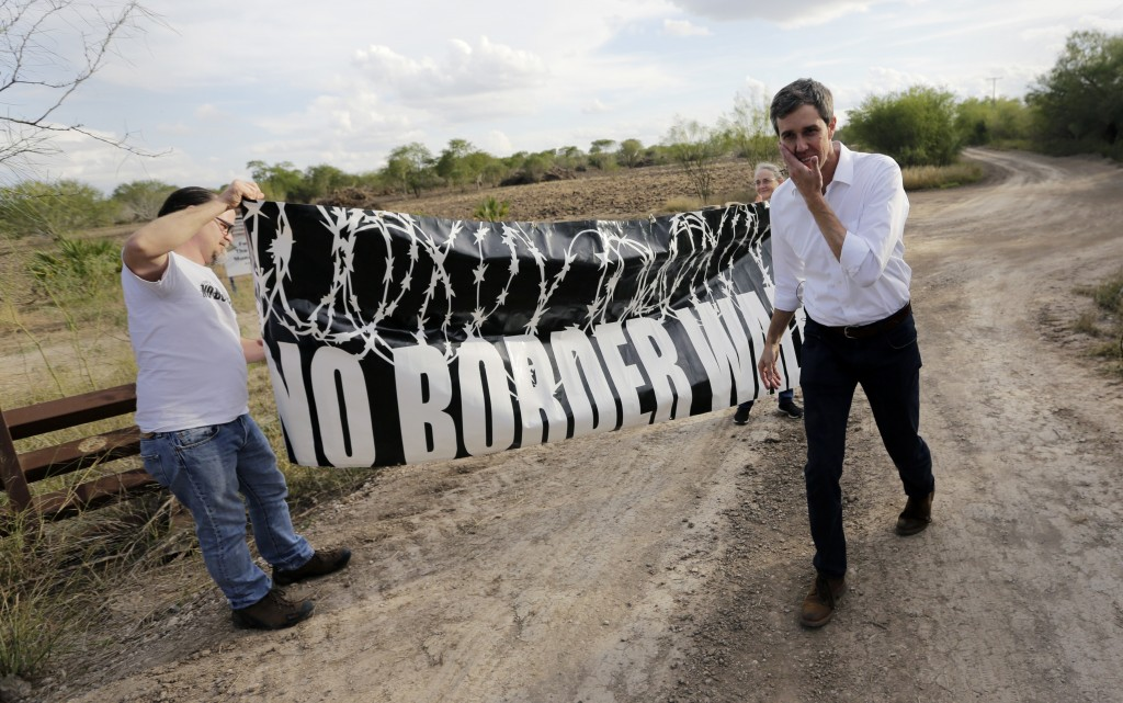 """FILE - In this Saturday, Jan. 6, 2018, file photo, Texas Democratic Congressman Beto O'Rourke, right, passes a """"No Border Wall"""" sign during a visit to"""