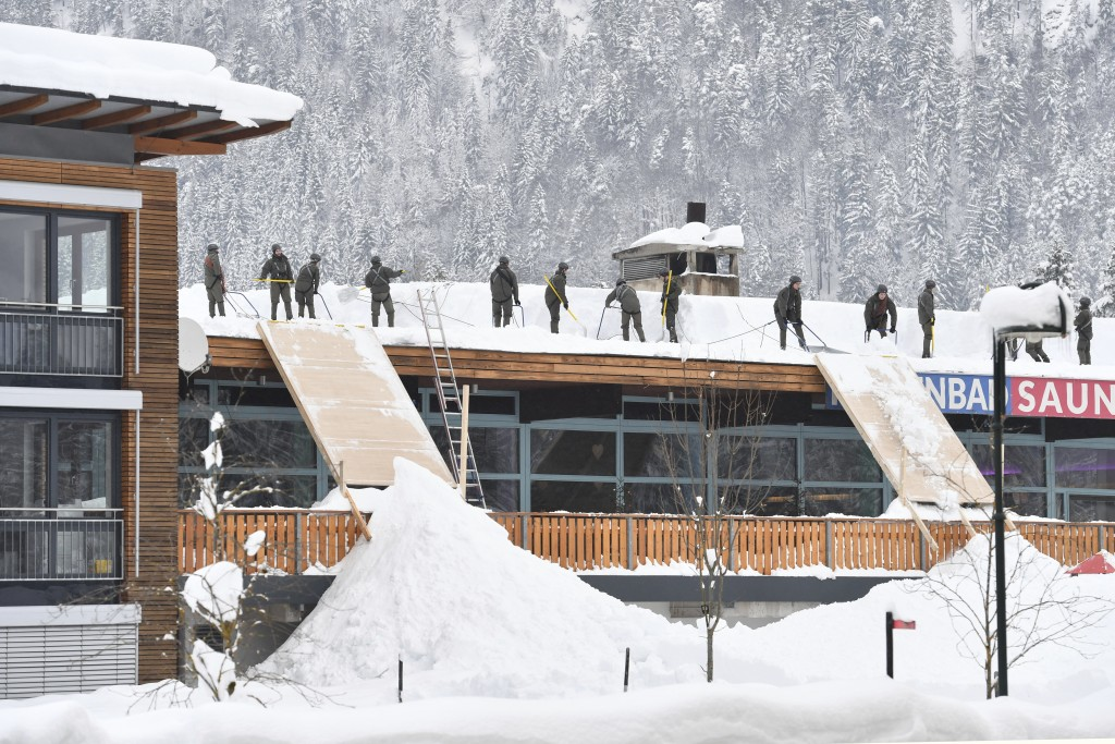 Solidiers from the Austrian Bundesheer clean a roof from snow on Saturday, Jan. 12, 2019 in Waidring. Austrian province of Tyrol.(AP Photo/Kerstin Joe