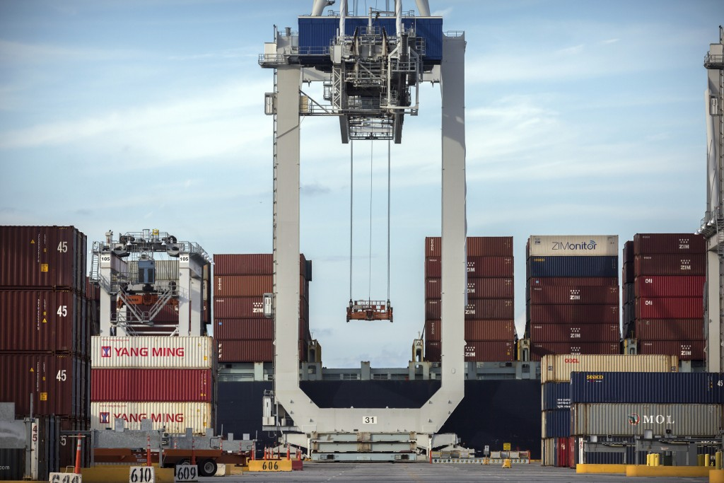FILE- In this July, 5, 2018, file photo photo, a ship to shore crane prepares to load a 40-foot shipping container onto a container ship at the Port o...