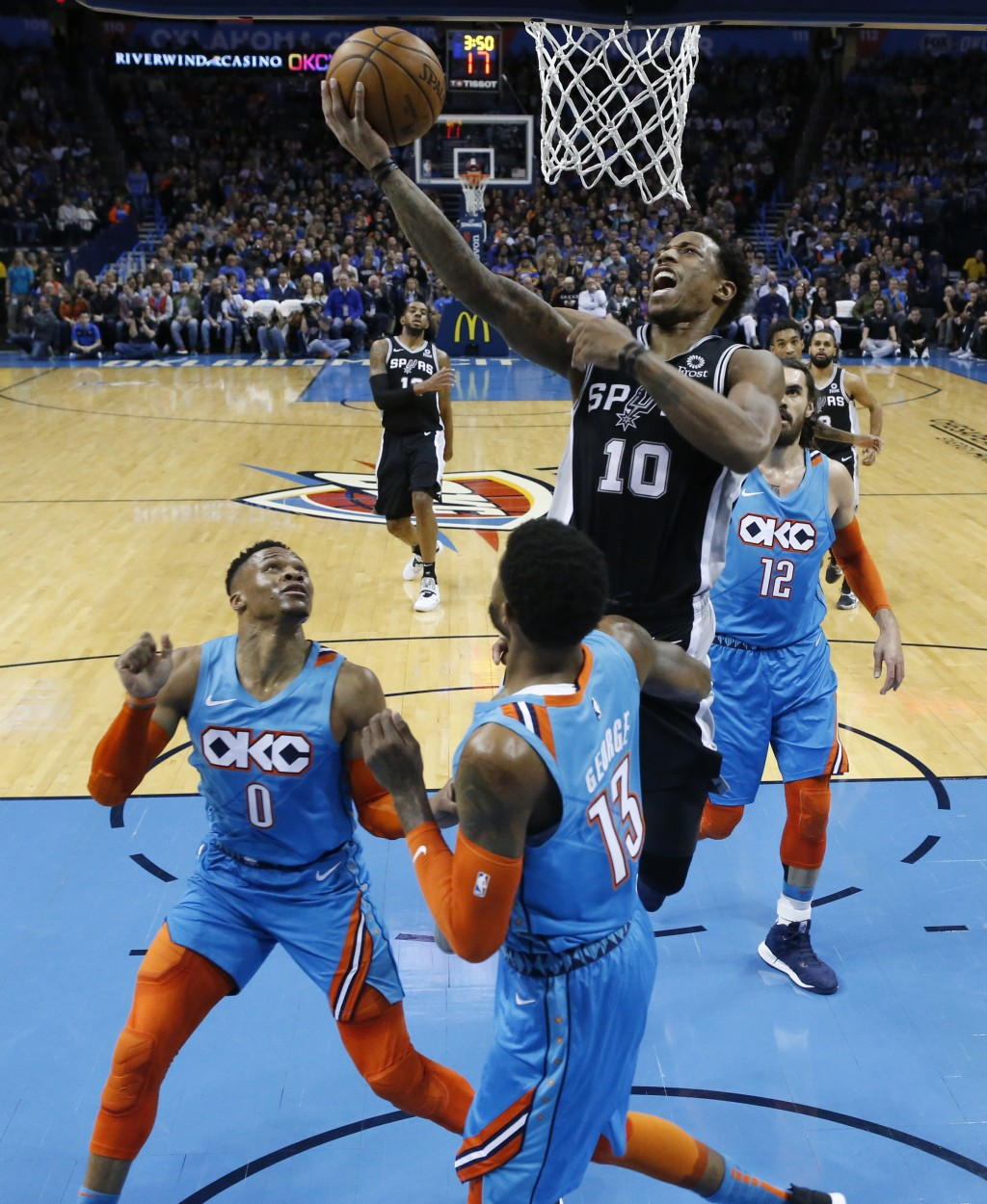 San Antonio Spurs guard DeMar DeRozan (10) goes up for a shot between Oklahoma City Thunder guard Russell Westbrook (0), forward Paul George (13) and