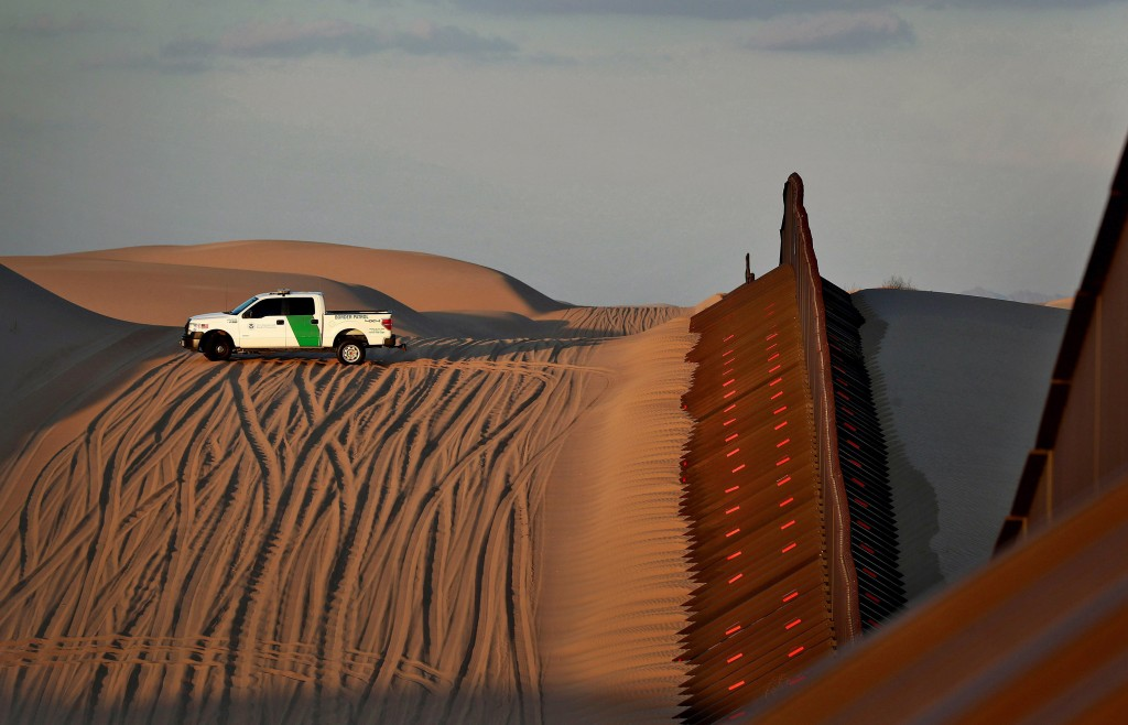 FILE - In this July 18, 2018 file photo, a U.S. Customs and Border Patrol agent patrols a section of floating fence at sunset that runs through Imperi