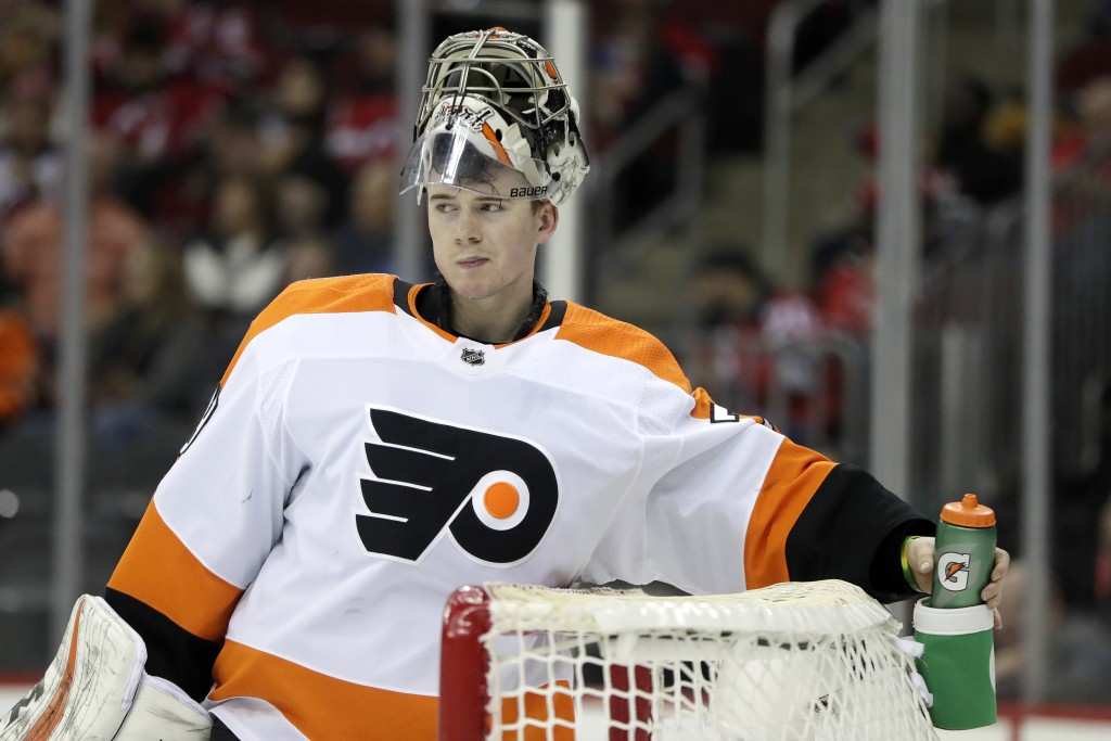 Philadelphia Flyers goaltender Carter Hart grabs his water bottle between plays against the New Jersey Devils during the second period of an NHL hocke