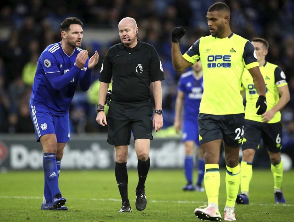 Cardiff City's Sean Morrison reacts after Match referee Lee Mason, center, overturns a penalty decision during the English Premier League soccer match