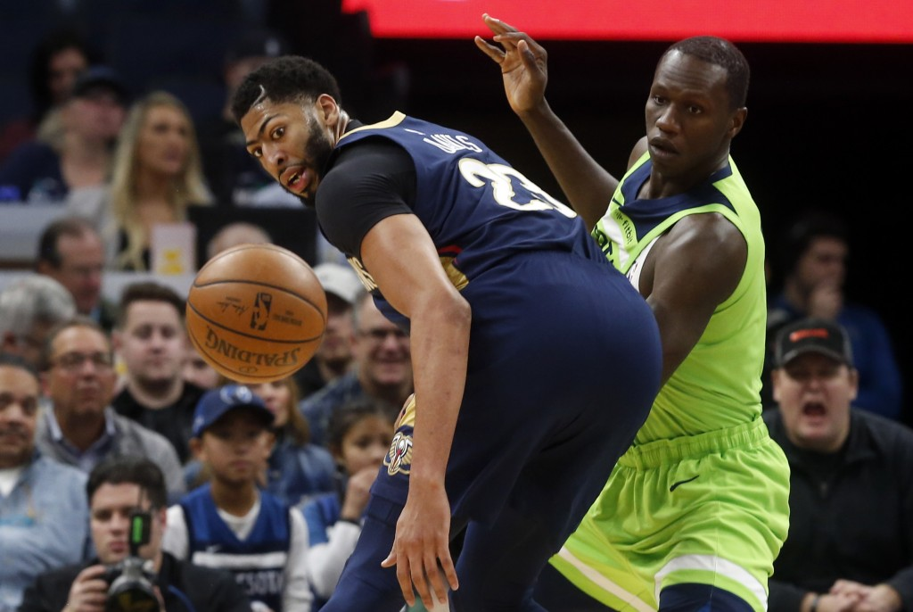 New Orleans Pelicans' Anthony Davis, left, looks at the ball as Minnesota Timberwolves' Gorgui Dieng, of Senegal, defends in the first half of an NBA