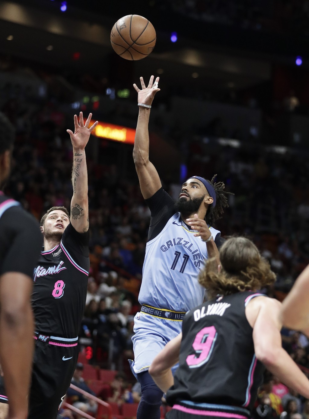 Memphis Grizzlies guard Mike Conley (11) shoots and scores against Miami Heat guard Tyler Johnson in the first half of an NBA basketball game on Satur