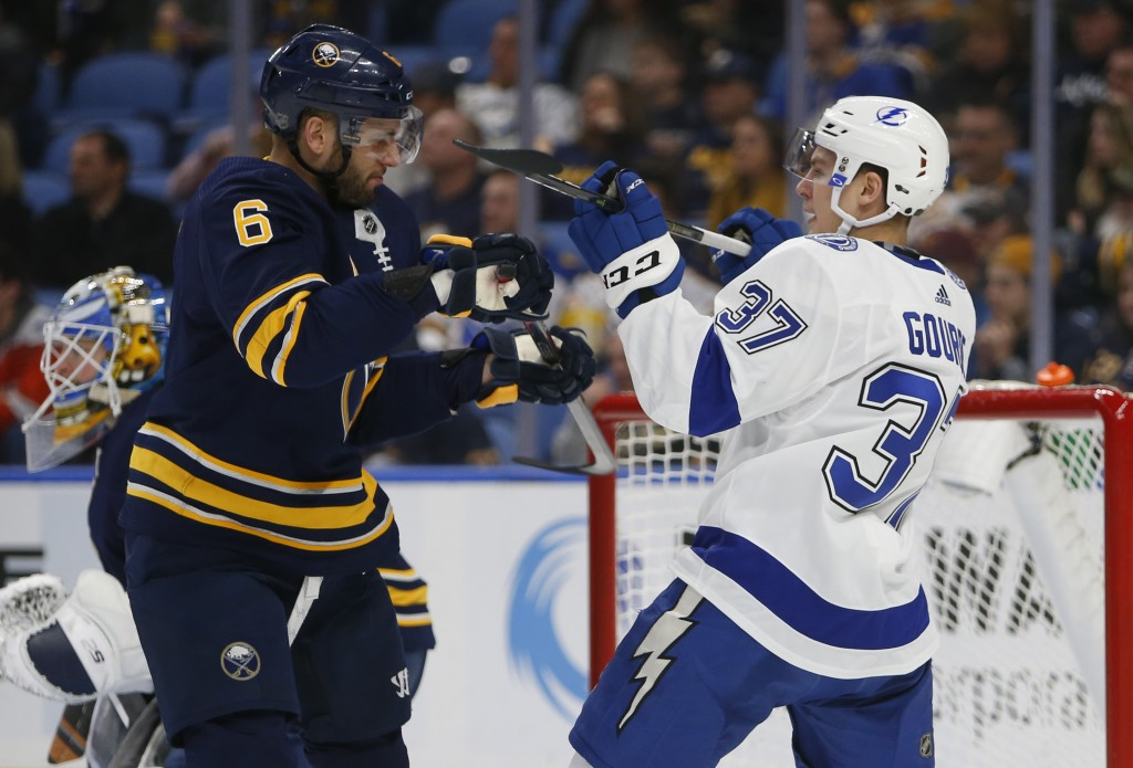 Buffalo Sabres defenseman Marco Scandella (6) and Tampa Bay Lightning forward Yanni Gourde (37) battle during the second period of an NHL hockey game,