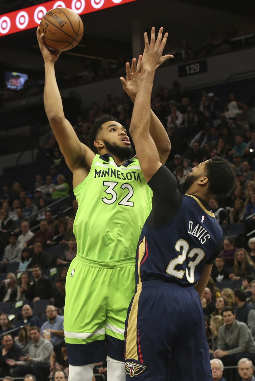 Minnesota Timberwolves' Karl-Anthony Towns, left, shoots over New Orleans Pelicans' Anthony Davis in the first half of an NBA basketball game Saturday