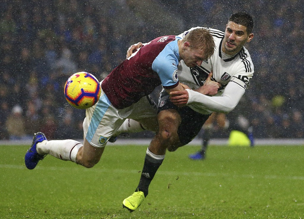 Fulham's Aleksandar Mitrovic, right, pulls back on Burnley's Ben Mee during the English Premier League soccer match between Burnley and Fulham at the