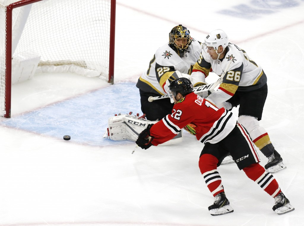 Chicago Blackhawks left wing Alex DeBrincat (12) slips the puck past Vegas Golden Knights goaltender Marc-Andre Fleury (29) for a goal during the firs