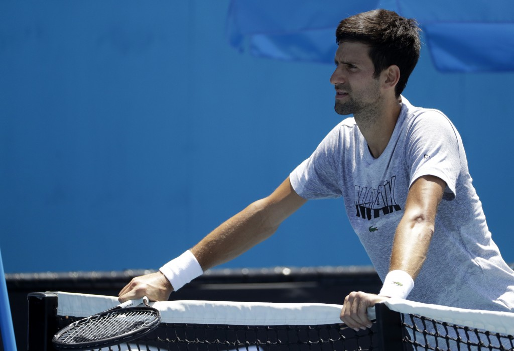 Serbia's Novak Djokovic rests on the net during a practice session at the Australian Open tennis championships in Melbourne, Australia, Sunday, Jan. 1