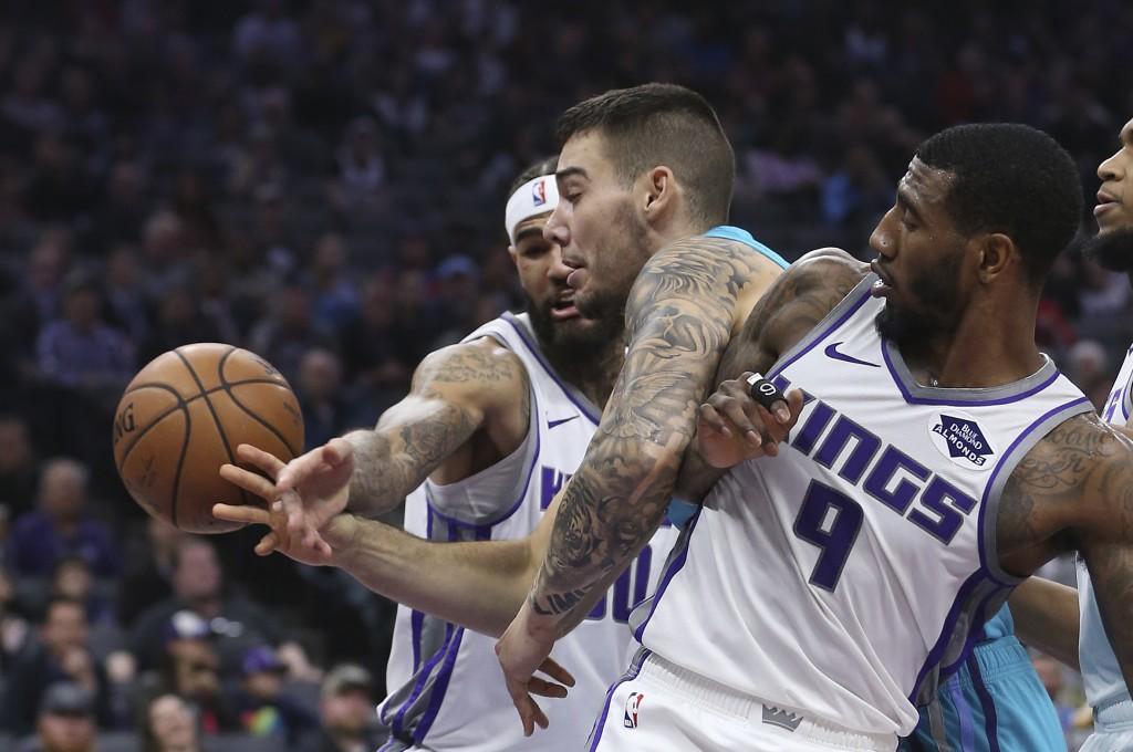 Charlotte Hornets center Willy Hernangomez, center, battles Sacramento Kings' Willie Cauley-Stein, left, and Iman Shumpert for the ball during the fir