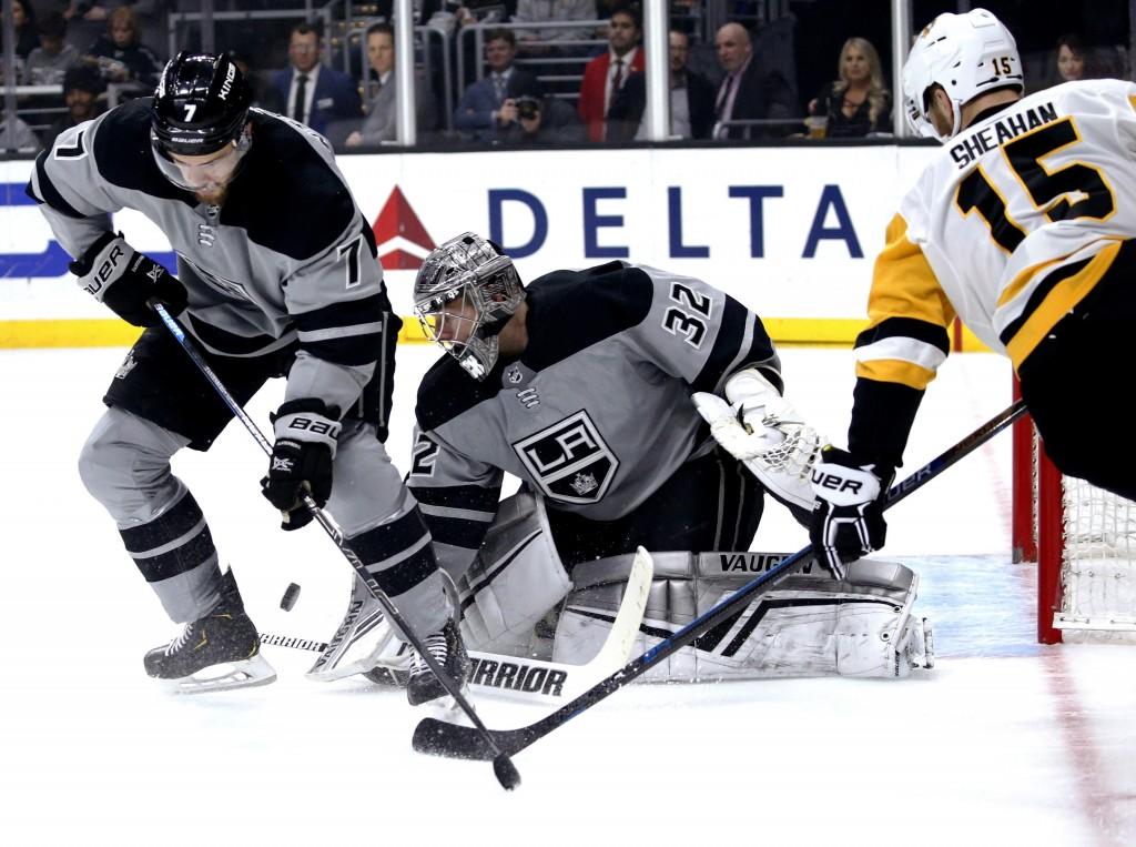 Los Angeles Kings goalie Jonathan Quick, center, protects the next while defenseman Oscar Fantenberg, left, and Pittsburgh Penguins forward Riley Shea