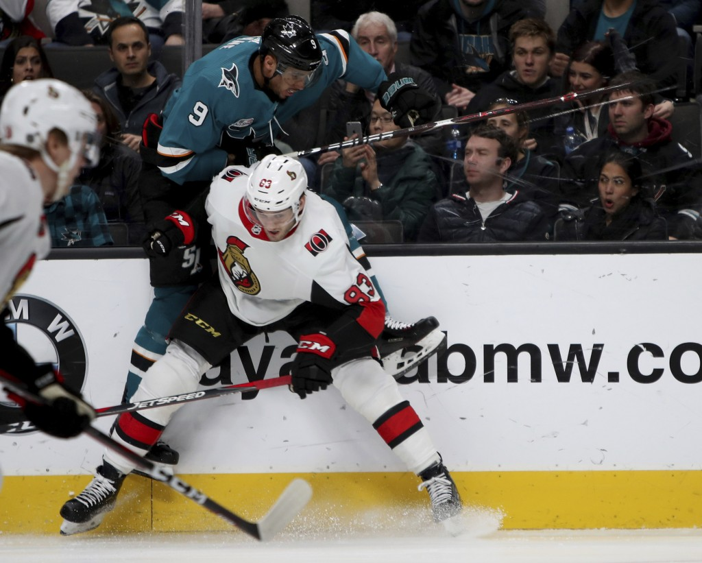 Ottawa Senators defenseman Christian Jaros (83) checks San Jose Sharks left wing Evander Kane (9) into the boards during the first period of an NHL ho