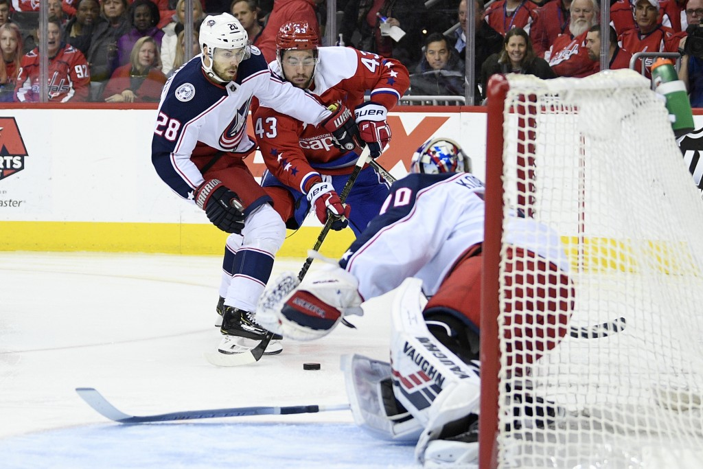 Washington Capitals right wing Tom Wilson (43) battles for the puck against Columbus Blue Jackets right wing Oliver Bjorkstrand (28), of Denmark, and