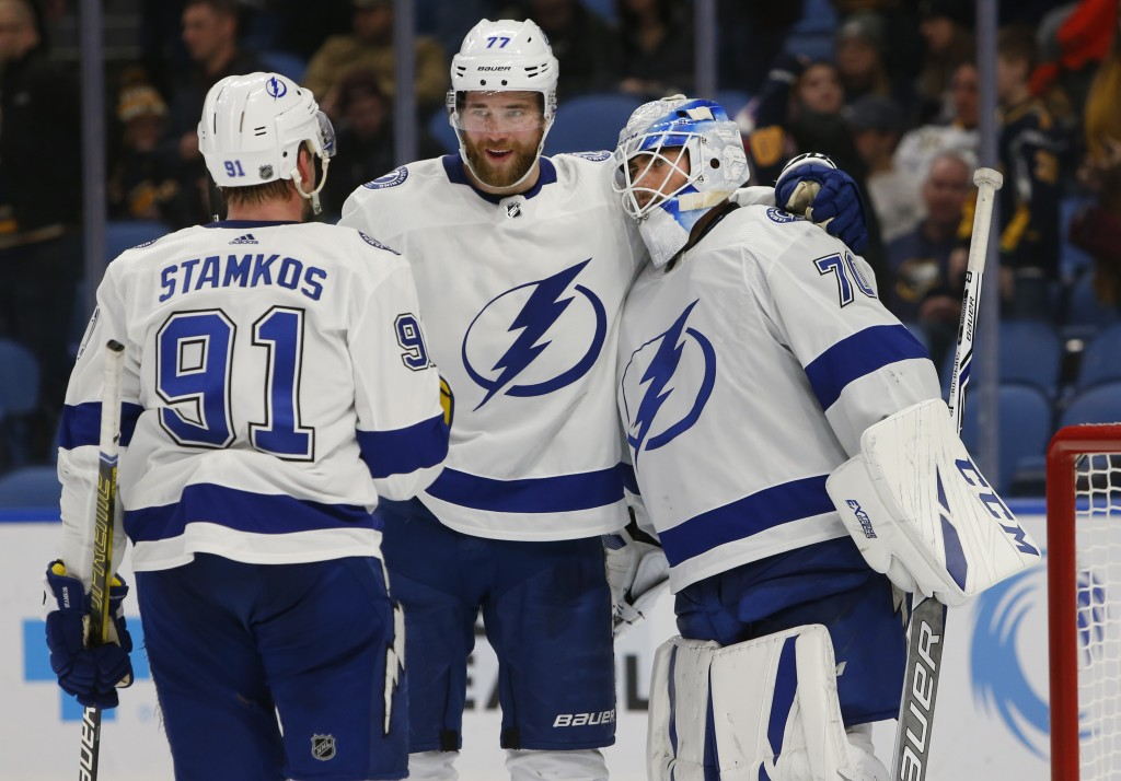 Tampa Bay Lightning's Steven Stamkos (91), Victor Hedman (77) and Louis Domingue (70) celebrate a victory over the Buffalo Sabres following the third