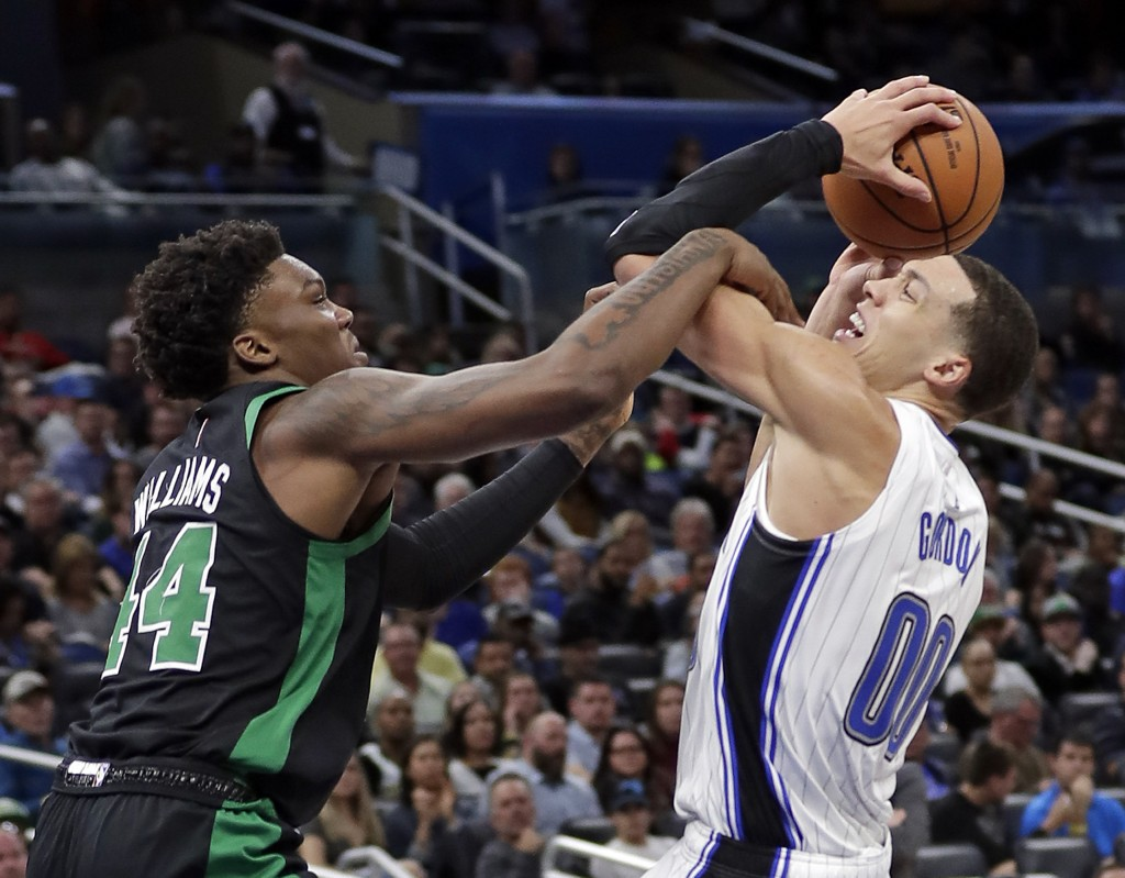 Boston Celtics' Robert Williams, left, fouls Orlando Magic's Aaron Gordon as he goes up for a shot during the first half of an NBA basketball game, Sa