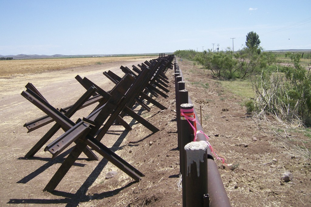 FILE - In this June 29, 2007 file photo, a portion of the U.S.- Mexico border near Columbus, New Mexico, shows the disputed metal pipe fence on the ri